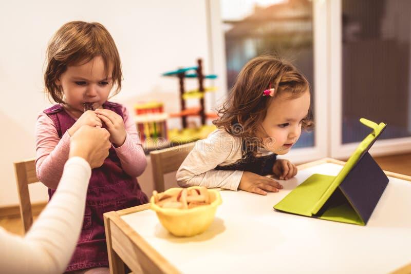 Förtjusande små systrar som spelar med en hemmastadd digital minnestavla royaltyfria bilder