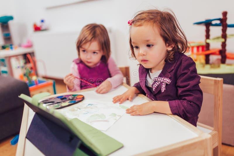 Förtjusande små systrar som spelar med en hemmastadd digital minnestavla royaltyfri foto