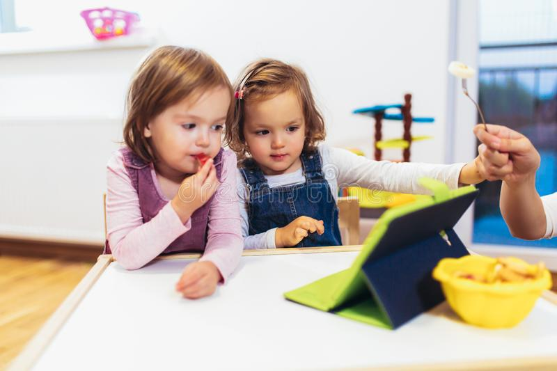 Förtjusande små systrar som spelar med en hemmastadd digital minnestavla fotografering för bildbyråer