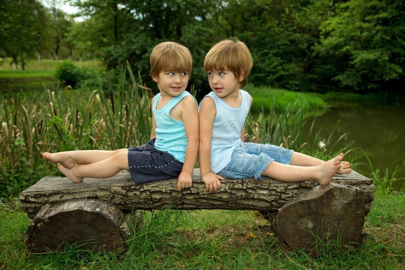 Förtjusande små tvilling- bröder som sitter på en träbänk, ler och ser de nära den härliga sjön arkivbild