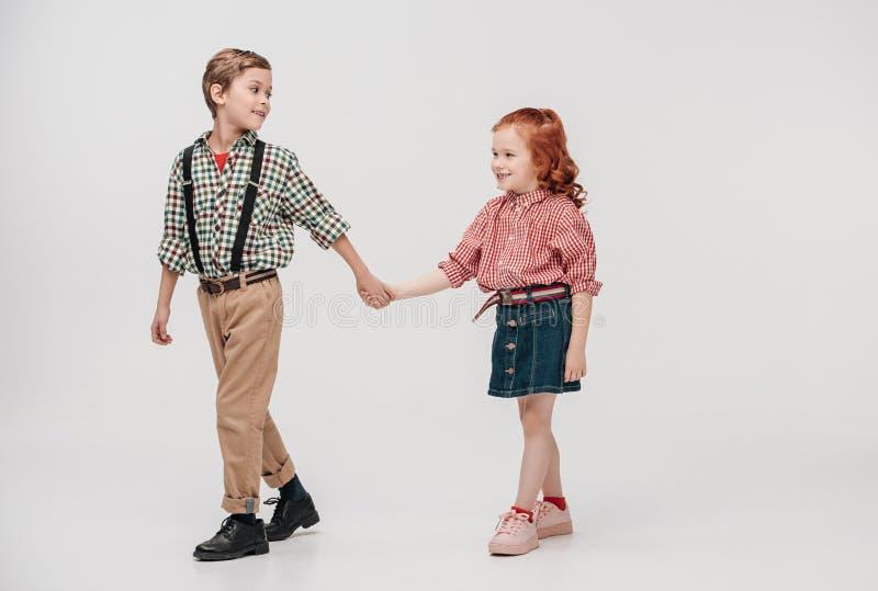 förtjusande små ungar som rymmer händer och tillsammans går royaltyfria bilder
