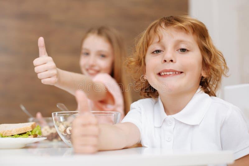 Förtjusande smileypojke som tycker om frukosten med hans syster royaltyfria bilder