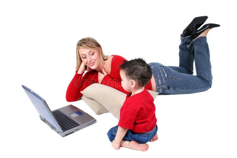 förtjusande son för moder för familjbärbar datorögonblick fotografering för bildbyråer