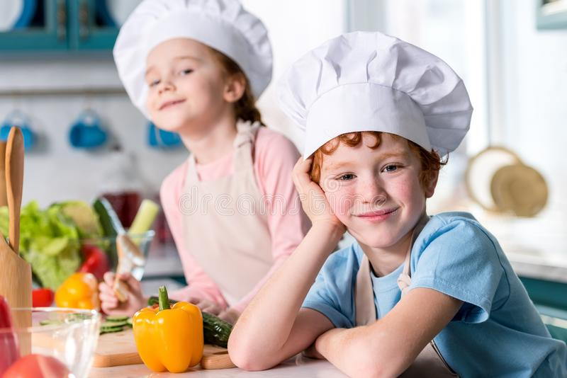 förtjusande syskon i kockhattar och förkläden som ler på kameran, medan laga mat fotografering för bildbyråer