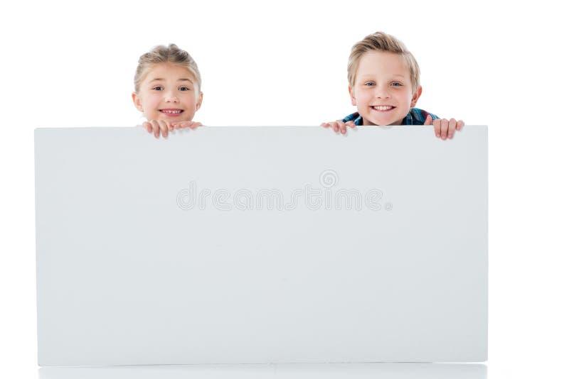 Förtjusande syskon som rymmer det tomma vita banret och ler på kameran arkivbild