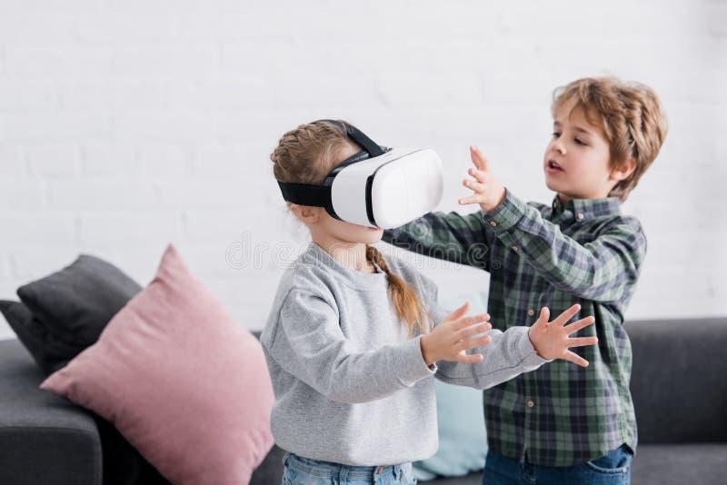 förtjusande syskon som spelar med virtuell verklighethörlurar med mikrofon fotografering för bildbyråer