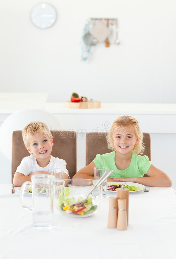 Förtjusande syskon som tillsammans äter en sallad royaltyfria bilder
