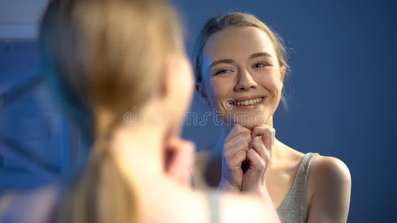 Förtjusande tonårs- flicka som ler på spegelreflexionen och att känna sig gladlynt och lyckligt royaltyfria bilder