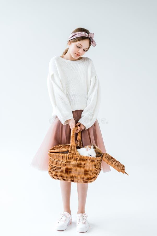 Förtjusande tonårs- flicka som rymmer den vide- korgen med päls- kaniner royaltyfri foto