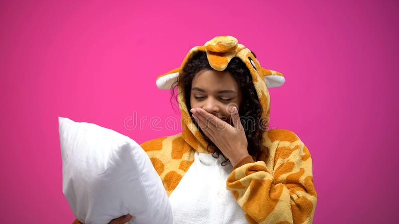 F?rtjusande tr?tt kvinna i giraffpyjamas som g?spar, innehavkudde, nattetid royaltyfri bild