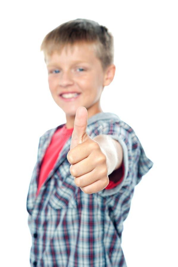 Förtjusande ung caucasian pojke som visar upp tum royaltyfri foto