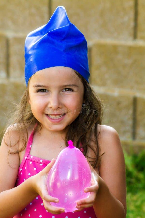 Förtjusande ung flicka som bär en Swimcap, och innehav ett vatten Balloo royaltyfri bild