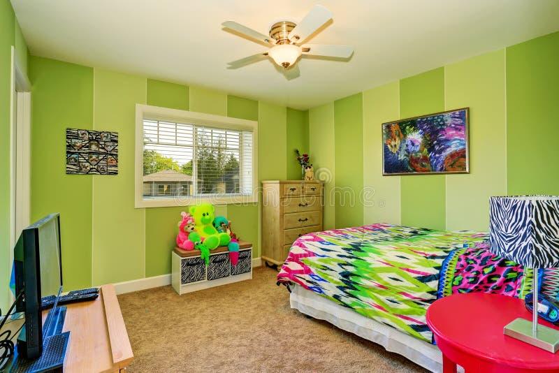 Förtjusande ungar hyr rum i grön färg med ljus färgrik sängkläder arkivbilder