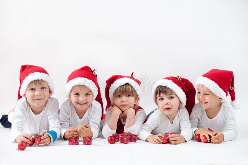 Förtjusande ungar med den santas hatten som ler på kameran arkivbilder