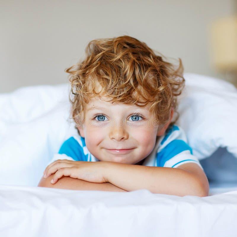 Förtjusande ungepojke, når att ha sovit i hans vita säng arkivfoto