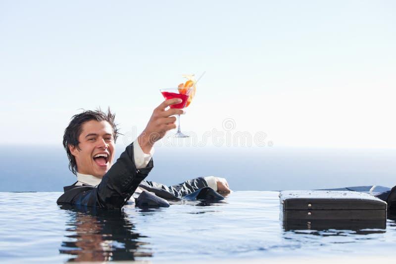 Förtjust affärsman som kopplar av i en simbassäng med en coctail fotografering för bildbyråer