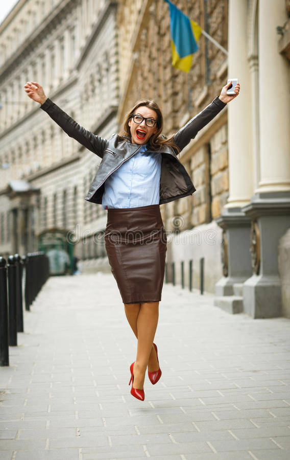 Förtjust banhoppning för affärskvinna för glädje, medan tala på smen royaltyfria bilder
