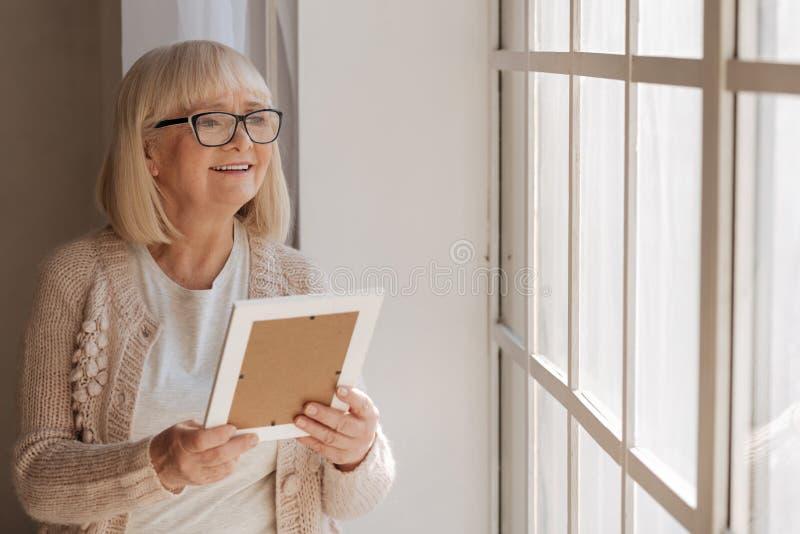 Förtjust drömlik kvinna som ser in i fönstret royaltyfria bilder