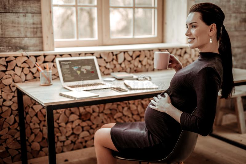 Förtjust gravid kvinna som tänker om hennes framtida barn royaltyfria foton