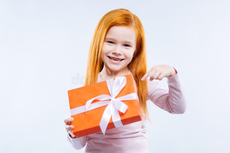 Förtjust gullig flicka som pekar på gåvan royaltyfri bild