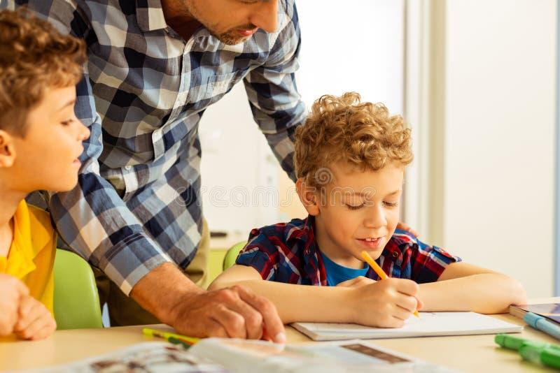 Förtjust gullig pojke som skriver i hans anteckningsbok arkivbild