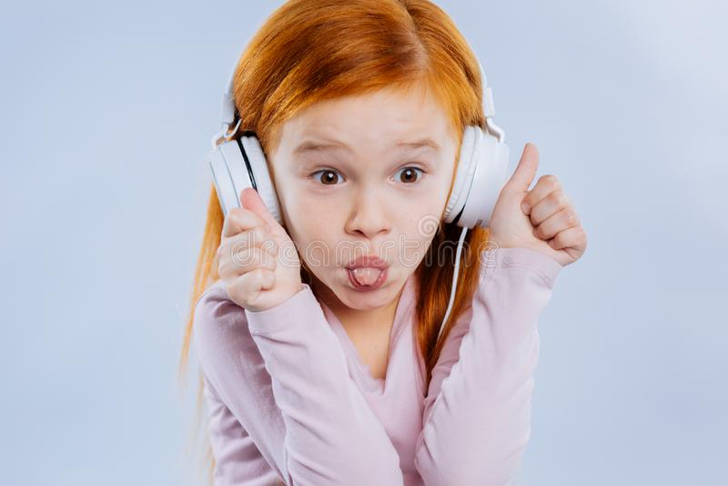 Förtjust gullig trevlig flicka som bär stor hörlurar arkivbilder