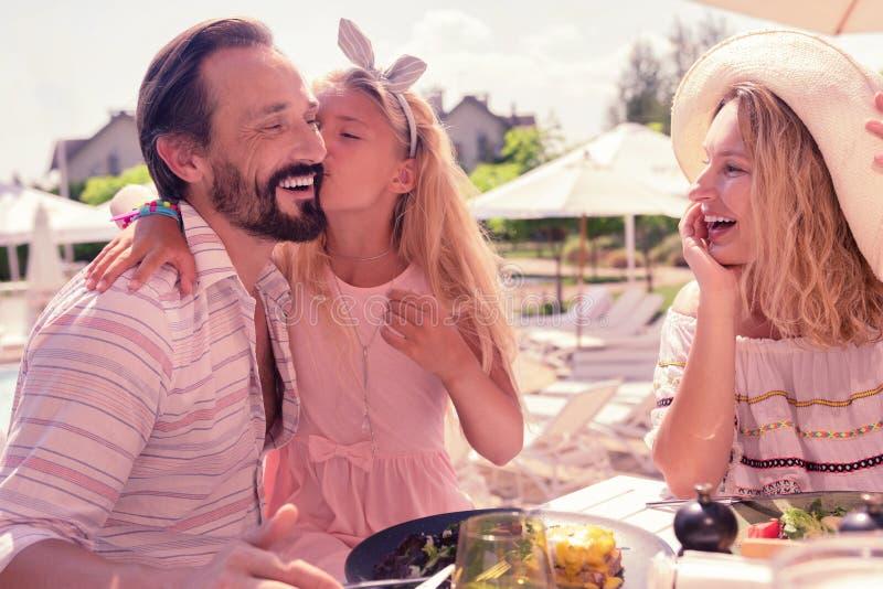 Förtjust gullig trevlig flicka som kysser hennes fader arkivfoto