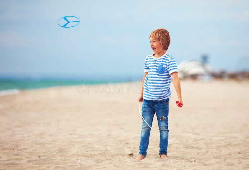 Förtjust gullig ung pojke, unge som har gyckel på stranden som spelar med propellerleksaken arkivbild