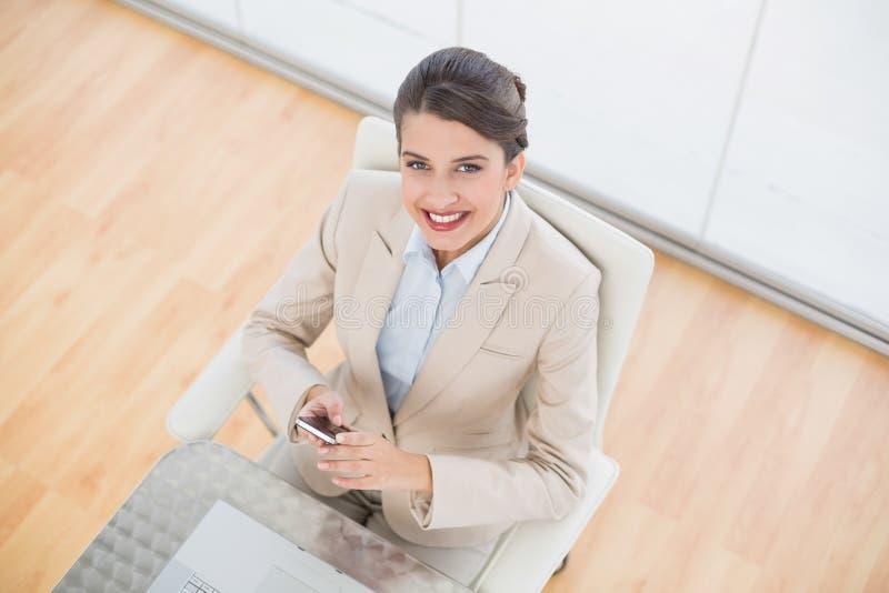 Förtjust ila den bruna haired affärskvinnan som använder en mobiltelefon fotografering för bildbyråer