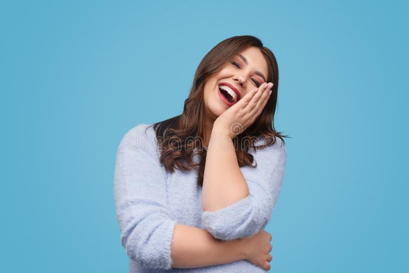Förtjust knubbig kvinna som skrattar på skämtet royaltyfria foton