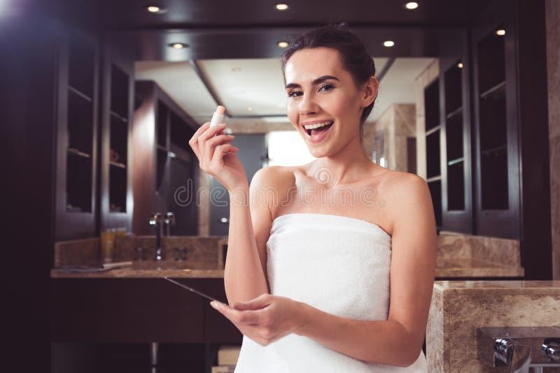 Förtjust kvinna som förskönar sig i badrum royaltyfri fotografi
