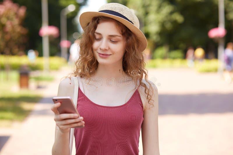 Förtjust lycklig ung dam som har angenämt ansiktsuttryck och att le uppriktigt som läser nyheterna, innehavsmartphone, genom att  arkivfoto