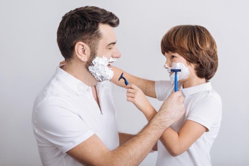 Förtjust man och pojke som går att raka arkivbild