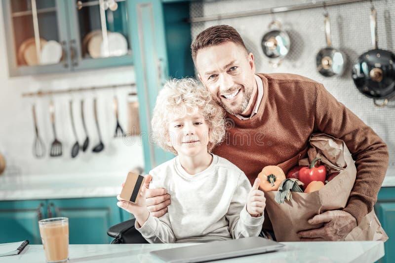 Förtjust manlig person som omfamnar hans son med förälskelse arkivbilder