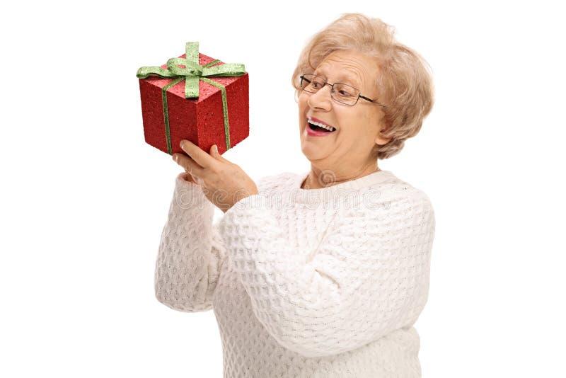 Förtjust mogen kvinna som rymmer en gåva royaltyfria bilder