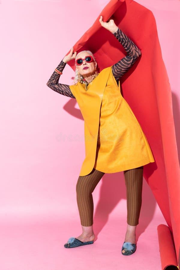 Förtjust moget kvinnligt anseende över rosa bakgrund arkivfoton