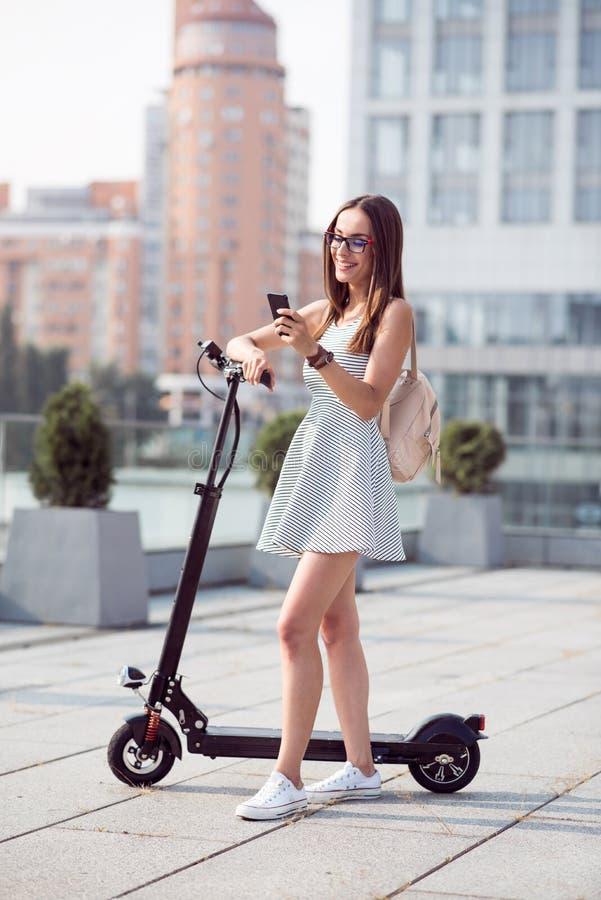 Förtjust positiv kvinna som står nära sparksparkcykeln royaltyfria bilder