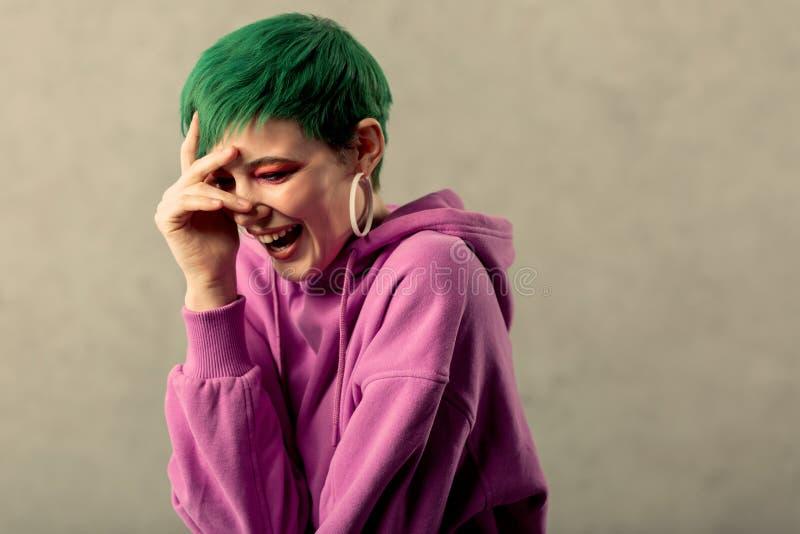 Förtjust positiv lycklig kvinna som trycker på hennes panna royaltyfri foto