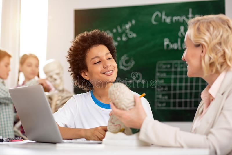 Förtjust positiv pojke som har en handledningkurs arkivfoto