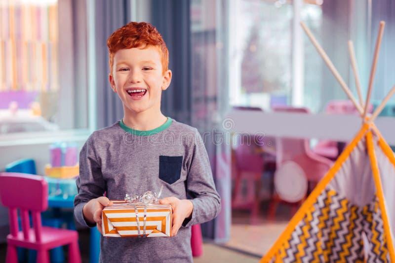 Förtjust rödhårig unge som håller leende på hans framsida royaltyfria bilder