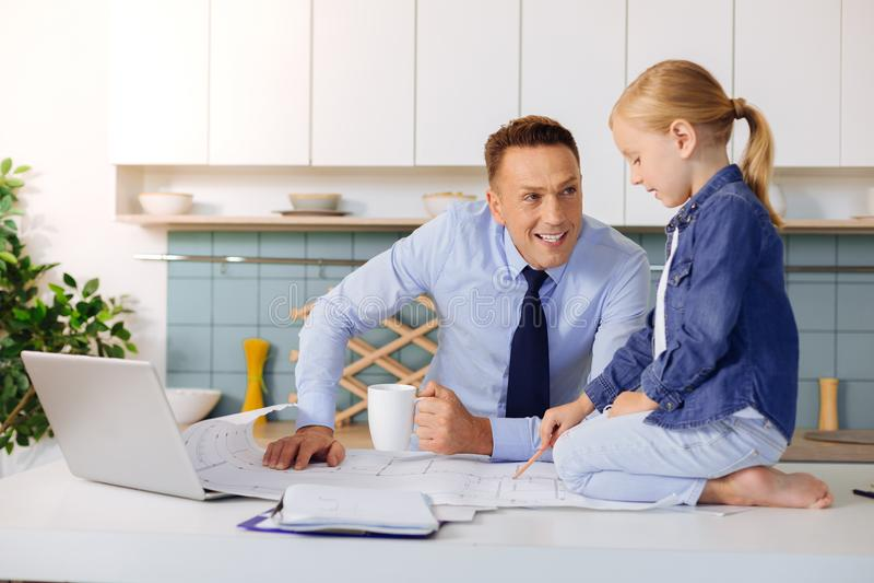 Förtjust smart flicka som hjälper hans fader med arbete arkivbilder