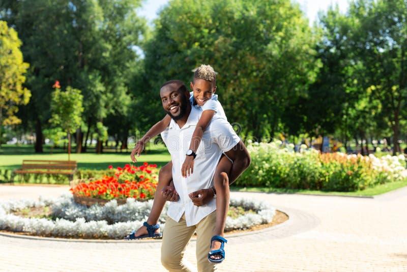 Förtjust stark man som bär hans son i hans händer fotografering för bildbyråer
