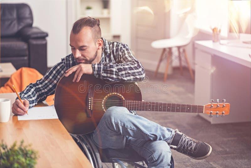 Förtjust stilfull manbenägenhet på hans gitarr arkivbild