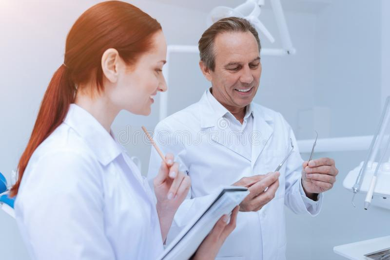 Förtjust stomatologist som håller två instrument i händer arkivbilder