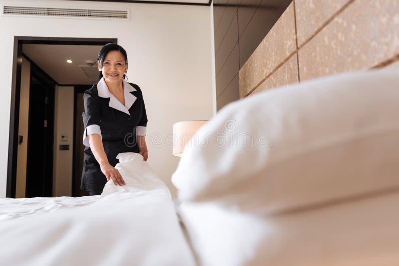 Förtjust yrkesmässig hotellhembiträde som är i ett positivt lynne arkivfoto