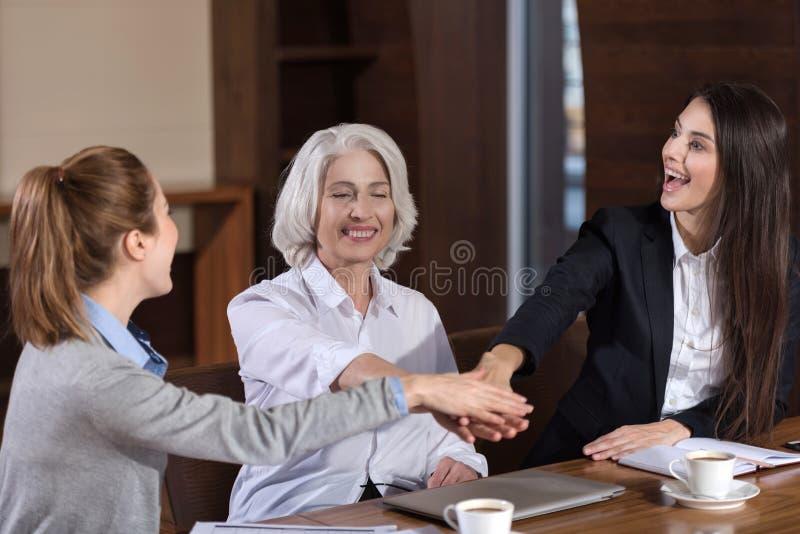 Förtjusta kollegor som rymmer varje andra händer arkivbild