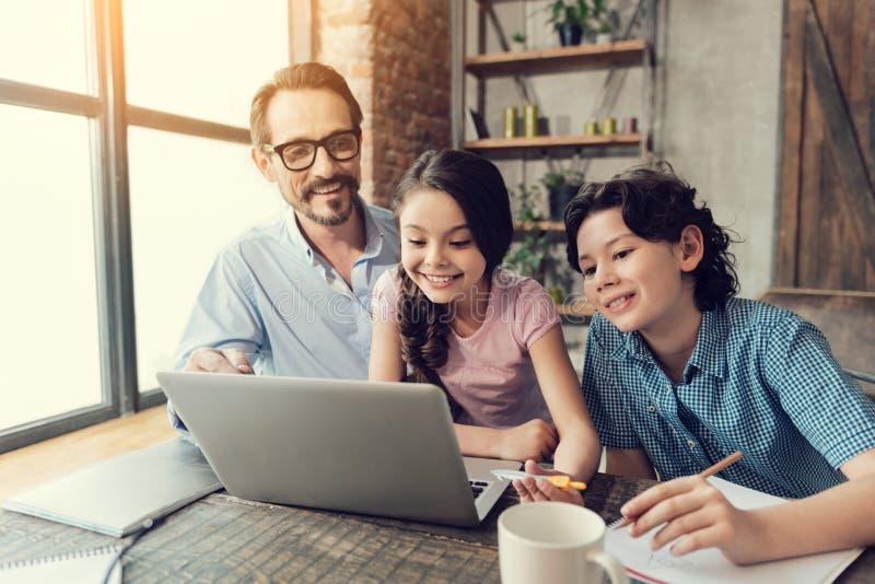 Förtjusta smarta barn som arbetar på bärbara datorn royaltyfria bilder