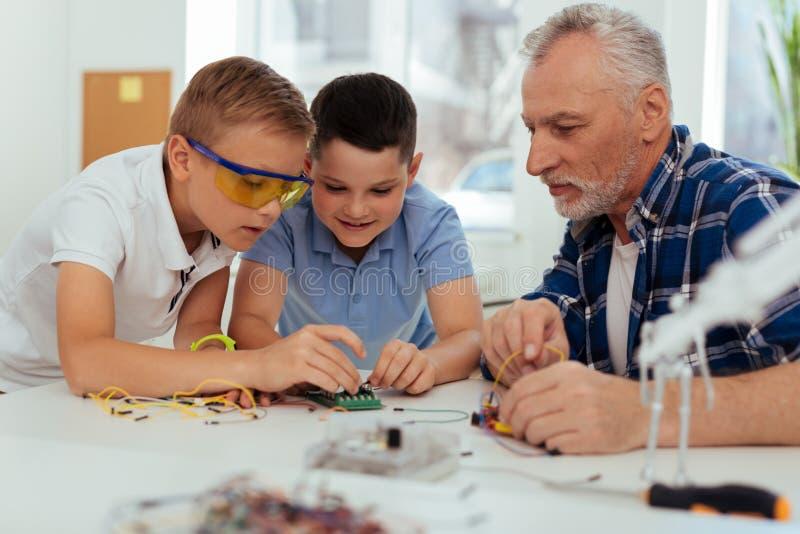 Förtjusta smarta barn som ser microschemen arkivbilder
