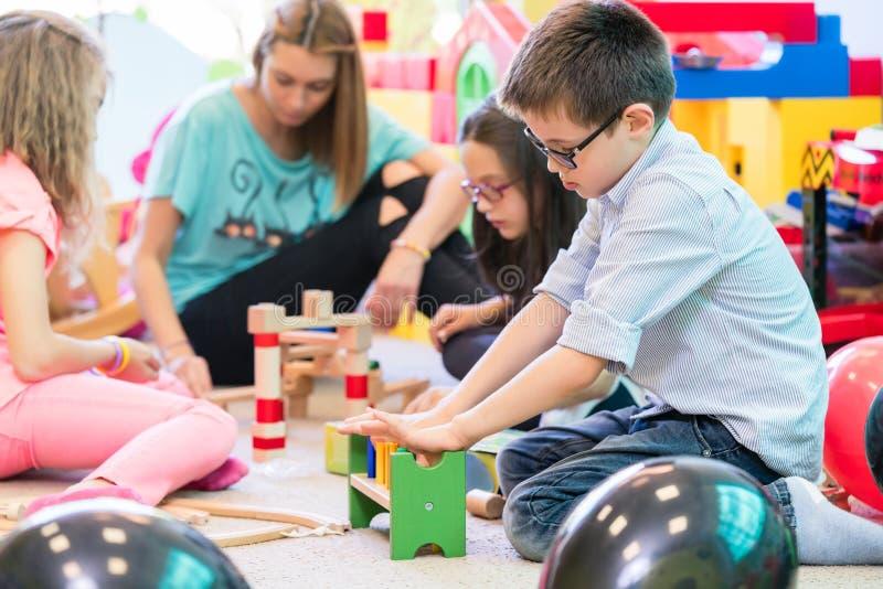 Förträningspojke som samarbetar med ungar under vägledning av dagisläraren arkivfoton