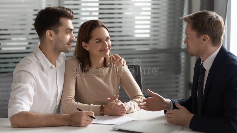 Förtroende chef som konsulterar unga par om kontrakt vid möte fotografering för bildbyråer